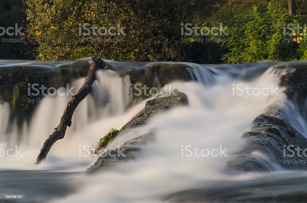 long exposure little watefall sorrounded by rocks and trees stock photo