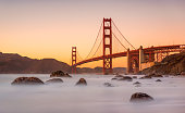 Long exposure photo in Marshall's Beach with Golden Gate Bridge in the background in San Francisco at sunset, California