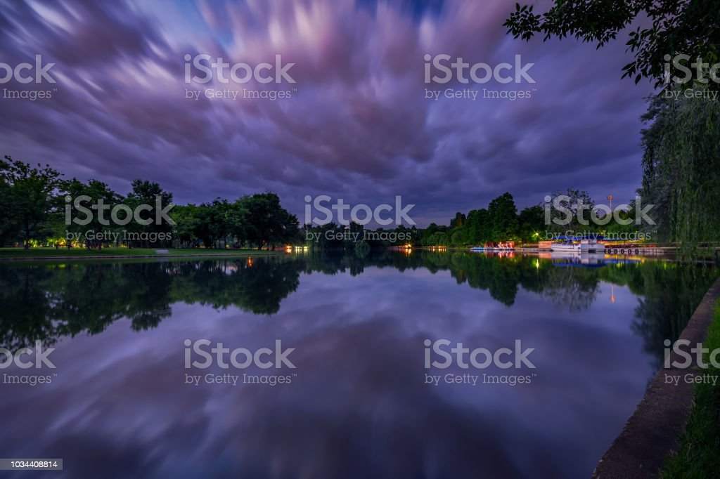 Long exposure night shot on a lake in the park with dramatic clouds and beautiful reflection in the water stock photo