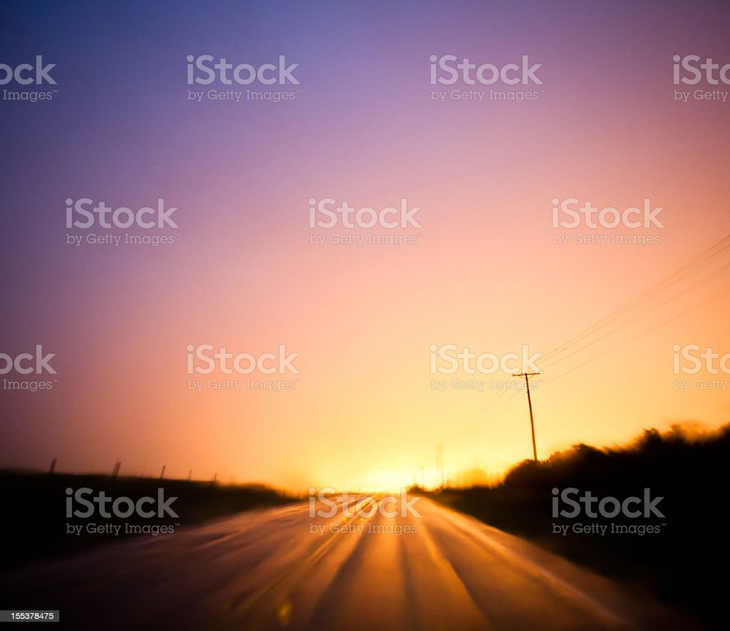 Long exposure of a brilliant sunset reflecting on country road royalty-free stock photo