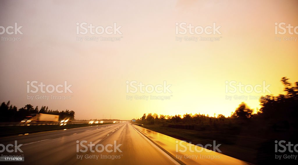 Long exposure of a brilliant sunset reflecting on the freeway royalty-free stock photo