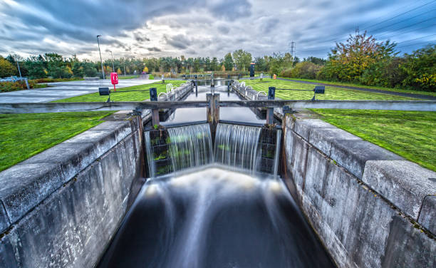 Long Exposure of a Water Lock Clear Water flowing down a Water Lock canal stock pictures, royalty-free photos & images