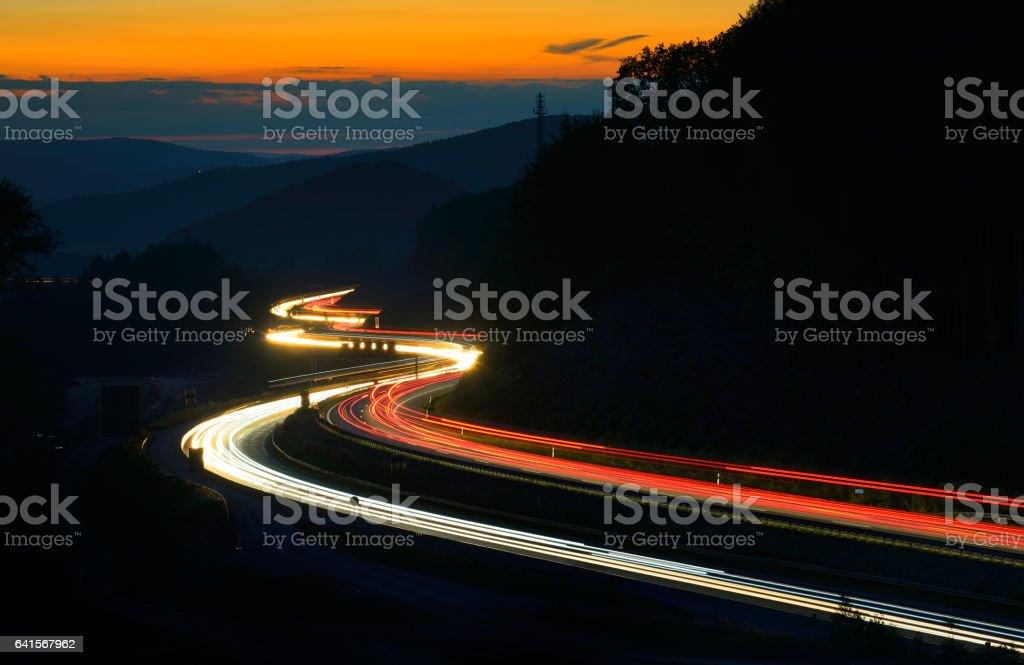Langzeitbelichtung von Auto leuchtet auf Autobahn Mäandern durch Hügel bei Sonnenuntergang – Foto