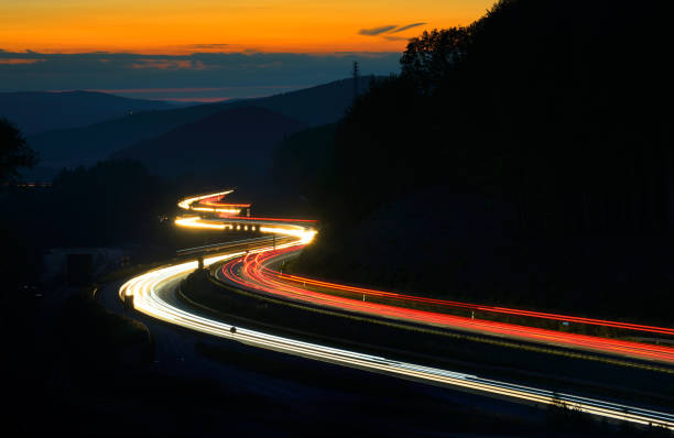 Long Exposure of Car Lights on Motorway Meandering through Hills at Sunset stock photo