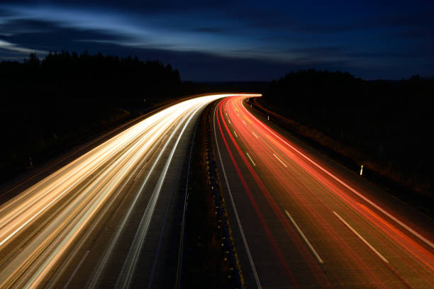 long exposure of car lights on winding motorway at night - highway stock photos and pictures
