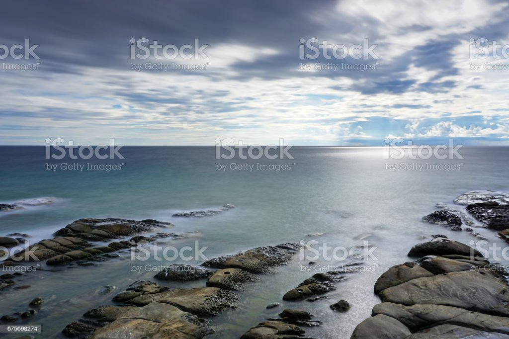 Long exposure of clouds and waves stock photo