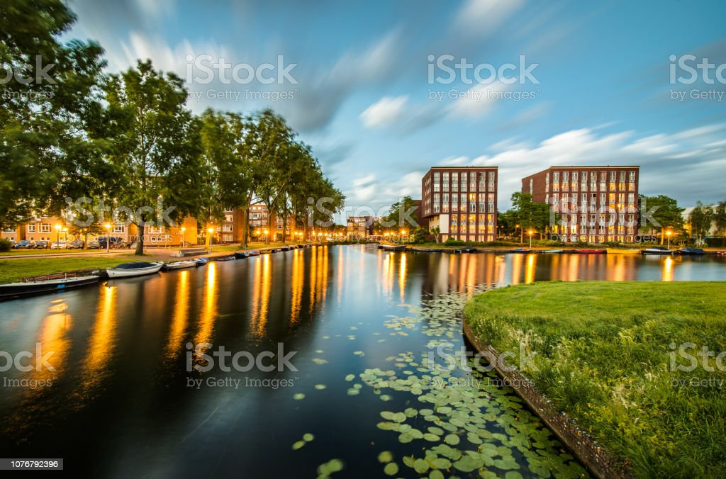 Long exposure of housing buildings and boats along a canal in Amsterdam stock photo