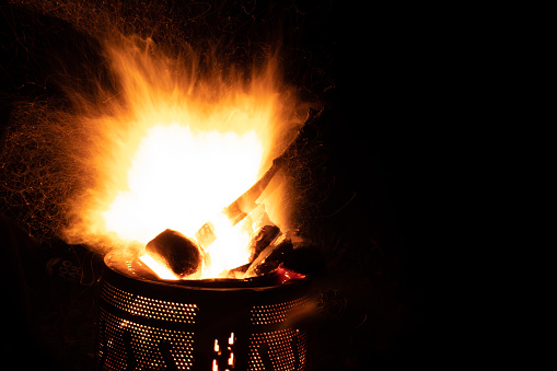 Long exposure of large campfire in the dark, with sparks flying out everywhere