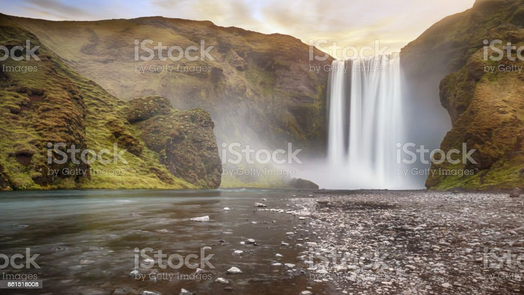 Long exposure of popular Skogafoss waterfall in southern Iceland, a classically-shaped waterfall set among steep cliffs with lush greenery. stock photo