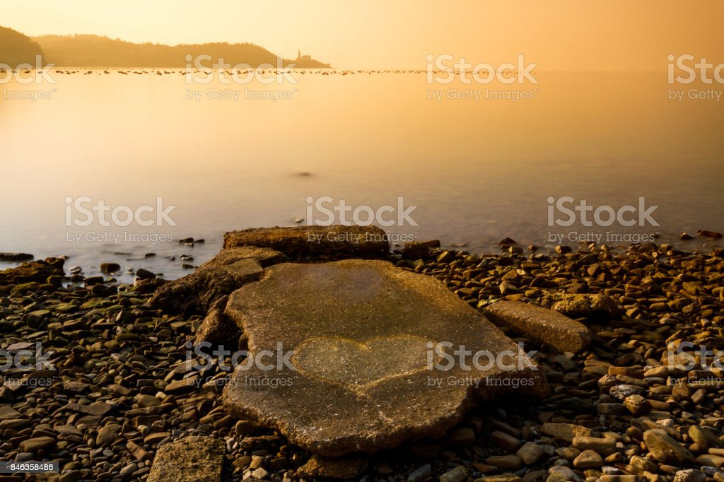 Long exposure of rock with the heart and Piran town silhouette in the background at sunset. stock photo