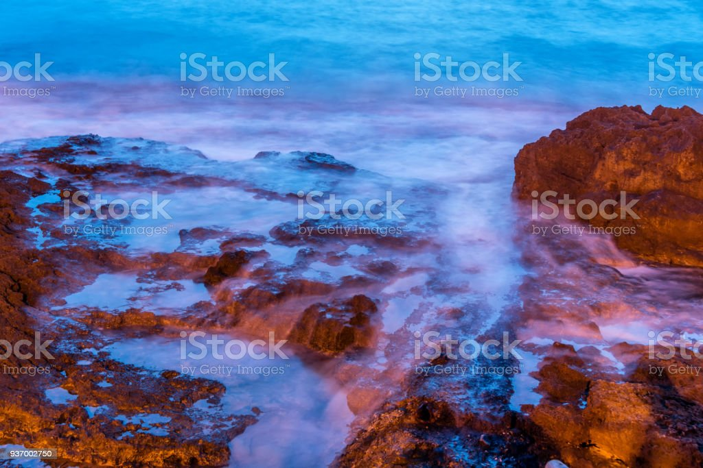Long Exposure of Rocks and Waves at Night in Orange and Blue stock photo