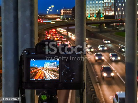 A long exposure photograph on the rear screen of a mirrorless camera, mounted on a tripod on an overpass to capture rush hour traffic.
