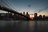 A long exposure of the Brooklyn Bridge and Downtown Manhattan from DUMBO during a red sunset afar.
