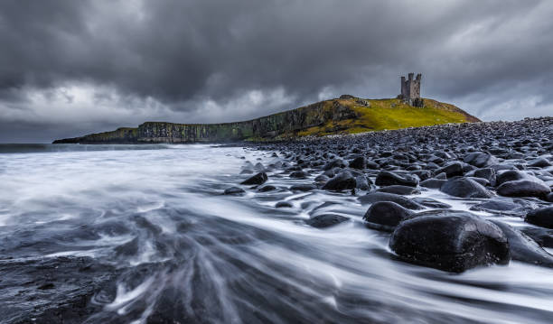 Long exposure of the sea and basalt rocks on the Northumberland coastline Long exposure of the sea and basalt rocks on the Northumberland coastline with Dunstanburgh Castle in background northeastern england stock pictures, royalty-free photos & images
