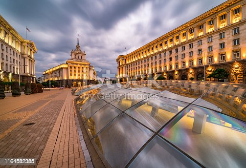 Panoramic long exposure photo from Sofia city centre in Bulgaria, Eastern Europe during twilight / rush hour with all the surrounding buildings night illumination. Including the iconic architecture of: the old house of parliament, ministry and presidency. Dragged shutter technique used to capture the blurred headlight/taillights from the road traffic. Shot on Canon full frame EOS R system for premium quality.