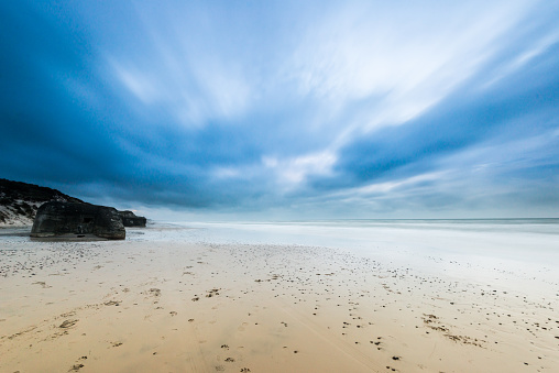 Long exposure photo of clouds rolling over a sand beach.