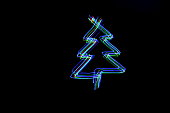 A light painting long exposure photo of a Christmas tree outline shape in fairy lights in a parallel lines pattern against a clean back background
