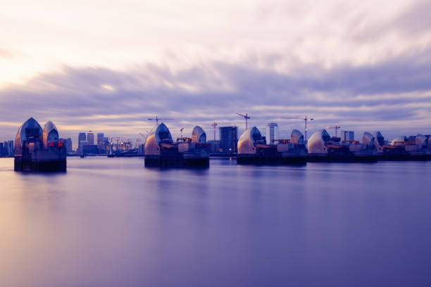 long exposure photography, thames barrier and canary wharf at sunset - barragem do roxo imagens e fotografias de stock