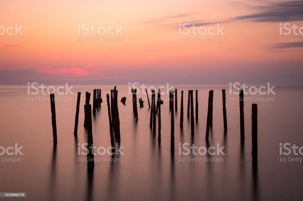 Long exposure. Piles stick out of the sea in the evening twilight.