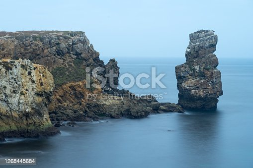 Long exposure seascape of the cliffs of Papoa island in Carvoeiro cape from the sea at sunrise in a cloudy day, Atlantic coast, Portugal