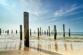 Long exposure seascape. Taken at the North Sea in Petten with the pole village in the sea, Blue sky, sun and shodows.