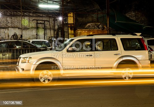 istock A long exposure shot of a large SUV car or vrhicle parked outside a garrage showing streaks of lights of passing by vehicles 1007087882