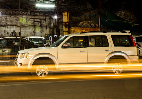 824108398 istock photo A long exposure shot of a large SUV car or vrhicle parked outside a garrage showing streaks of lights of passing by vehicles 1007087882