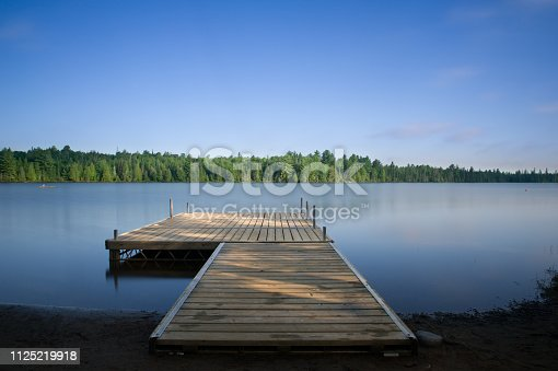 Wooden dock on a calm lake at the cottage in Ontario, Canada.
