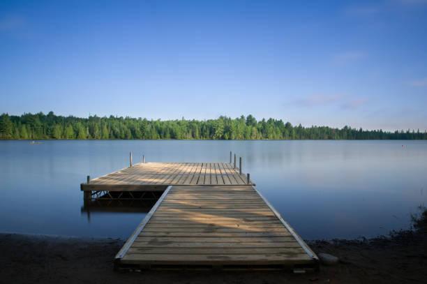tir longue exposition d'un quai en bois sur le lac soyeux - jetée photos et images de collection