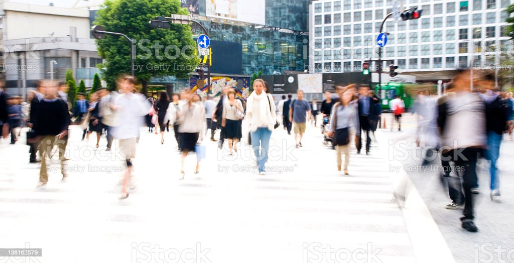 Long exposure shot of commuters crossing the road in the day royalty-free stock photo