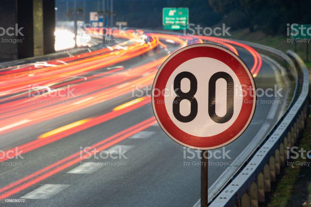 Longue exposition coup de panneau de signalisation indiquant la limite de vitesse de 80 km/h sur une route pleine de voitures en mouvement flou pendant la nuit - Photo