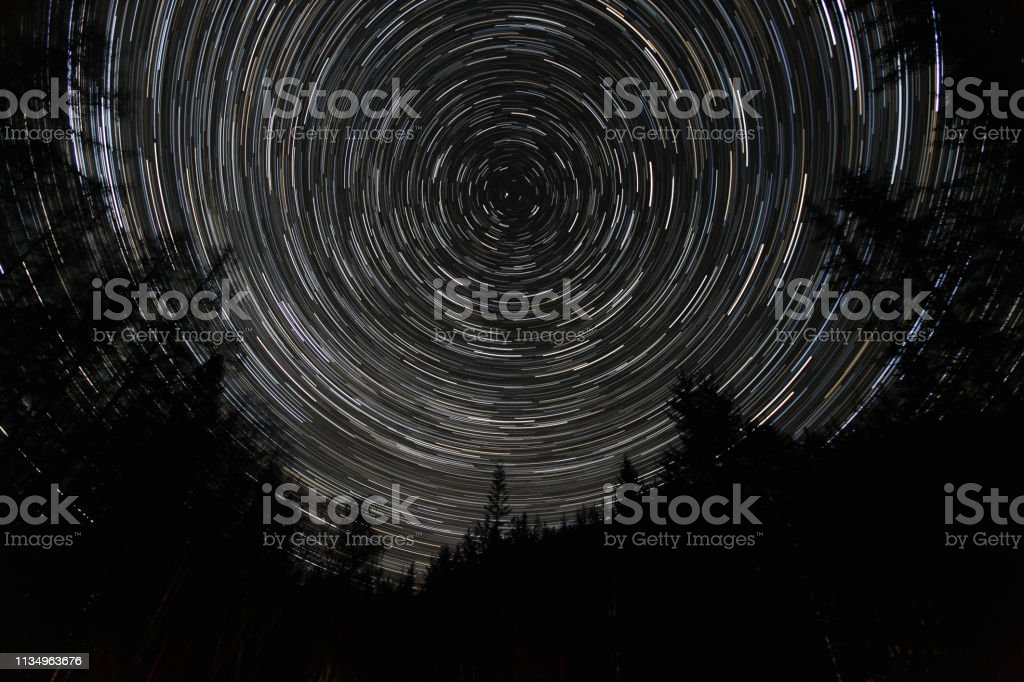 Long Exposure Star Trails in forest with North Star (Polaris) in centre stock photo