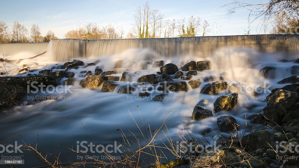 long exposure watefall sorrounded by rocks and trees stock photo