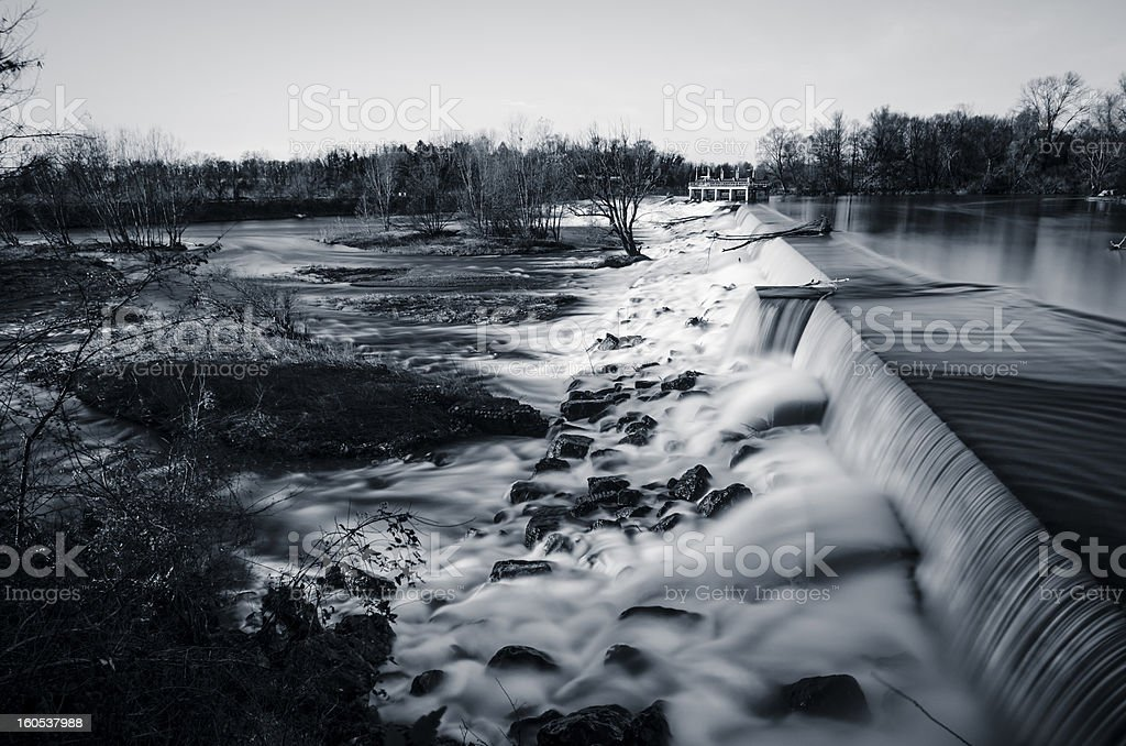 long exposure watefall sorrounded by rocks and trees, toned image stock photo