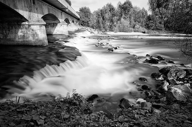 long exposure waterfall under a bridge in black and white foto