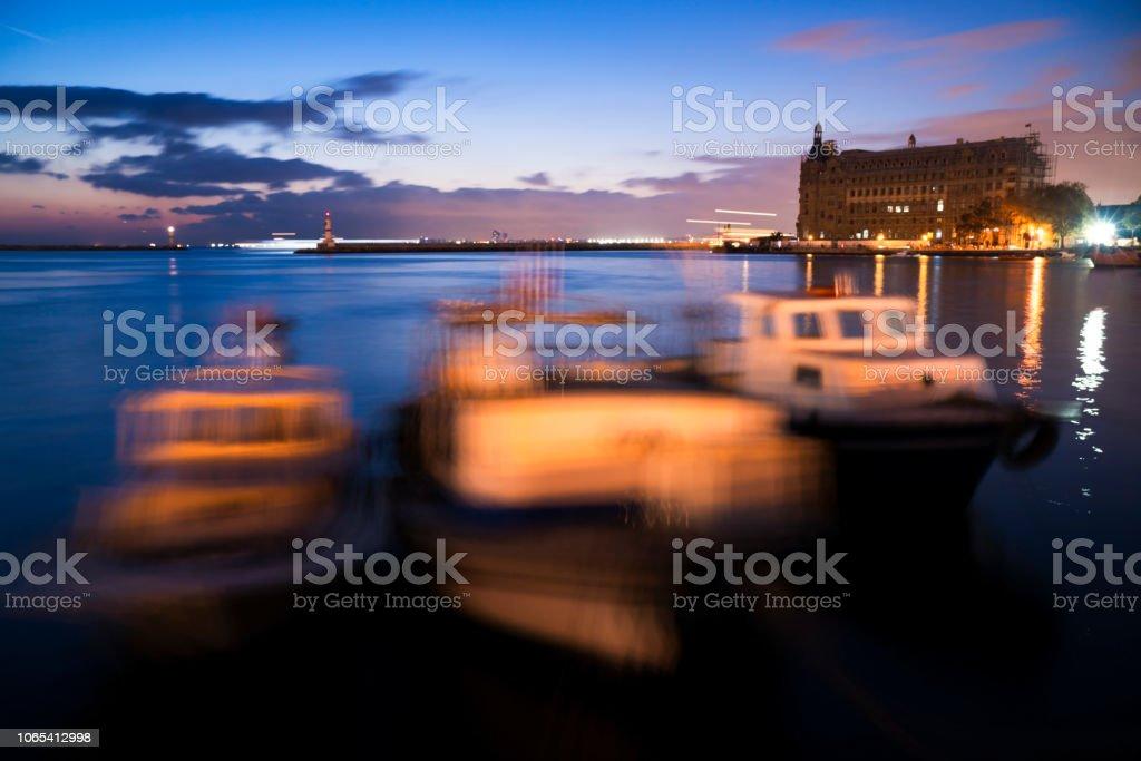 Long exposured fishing boats and Haydarpasa Train Station Building at Istanbul Kadikoy stock photo
