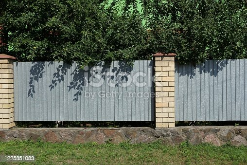 istock long fence wall made of gray metal and white bricks 1225851083