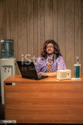 618210072 istock photo Long Hair Shaggy Looking Computer Tech Guy in Retro Office 155439173