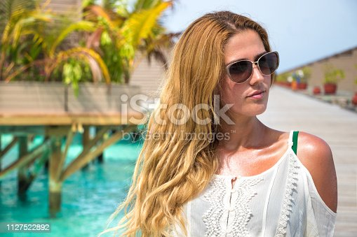 883117662 istock photo Long haired beautiful girl in front of water villas on wooden pier 1127522892