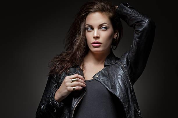 langhaar-brunette frau tragen lässige street-kleidung - lederjacke mit kapuze damen stock-fotos und bilder