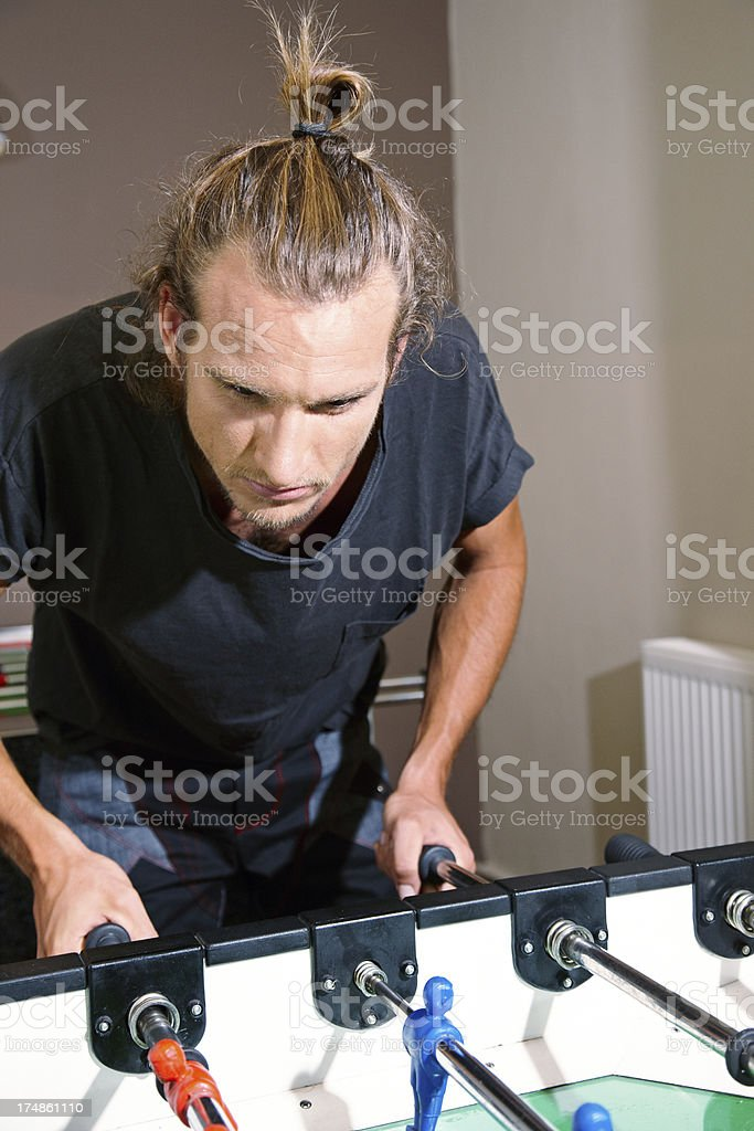 Long haired caucasian man playing table football royalty-free stock photo