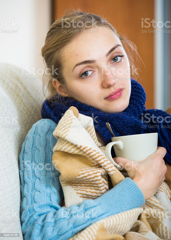 Long haired girl having cold and staying in bed stock photo