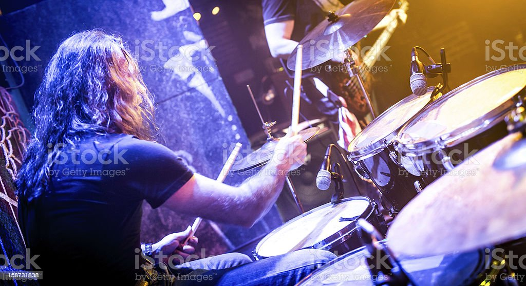 A long haired male playing the drum set stock photo