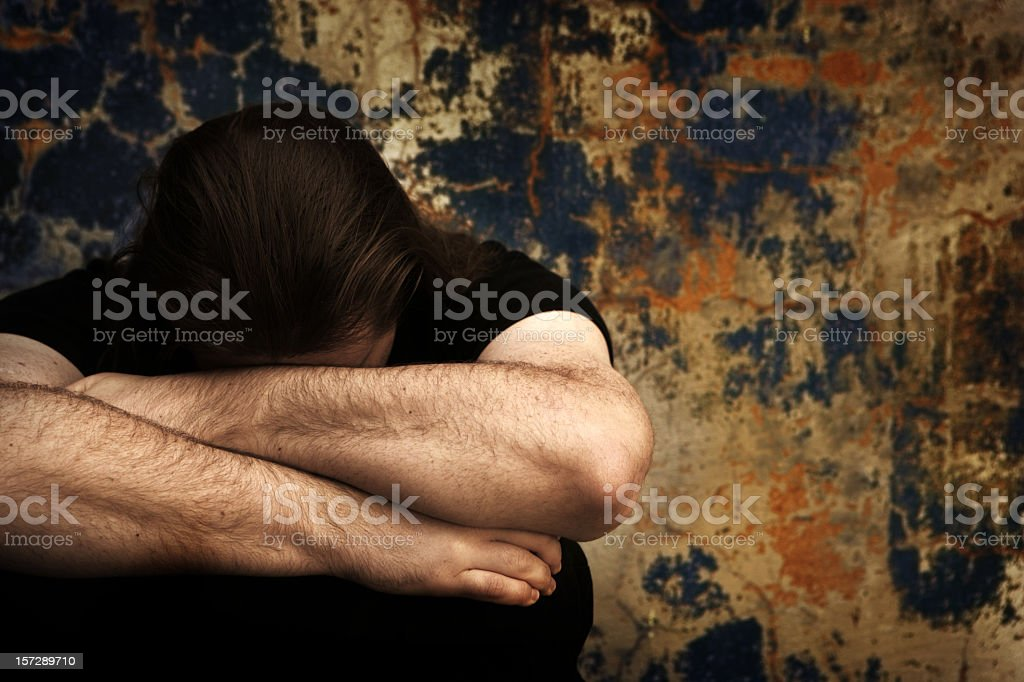 Long haired man unhappy hugging knees in bleak background royalty-free stock photo