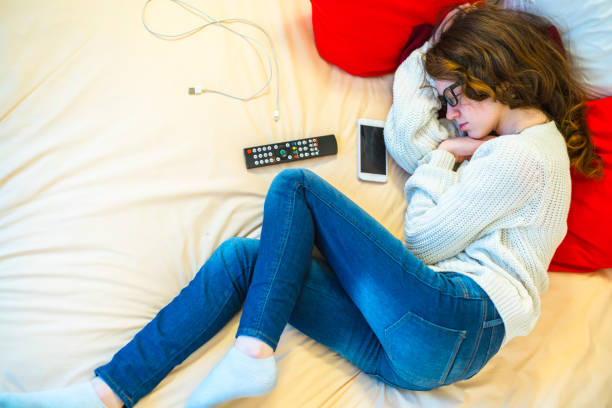 Long haired pretty 16-years-old teenager girl sleeping on the bed in the hotel room during the travel - foto stock