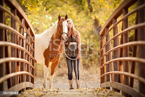 Teen girl and horse standing near bridge in autumn nature setting.
