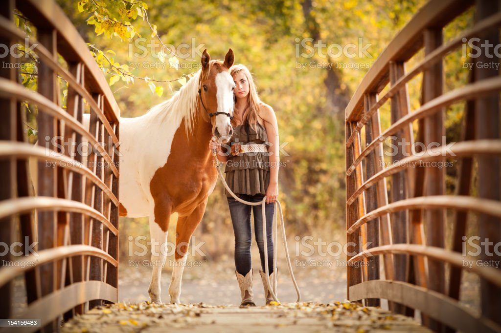 Long Haired Teen Girl Standing With her Horse on Bridge stock photo