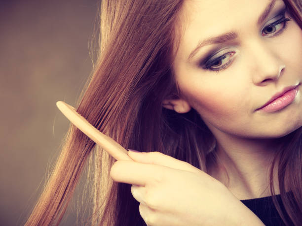 Long haired woman combing her hair. stock photo
