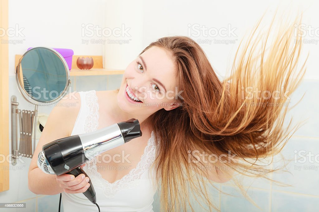 long haired woman drying hair in bathroom stock photo