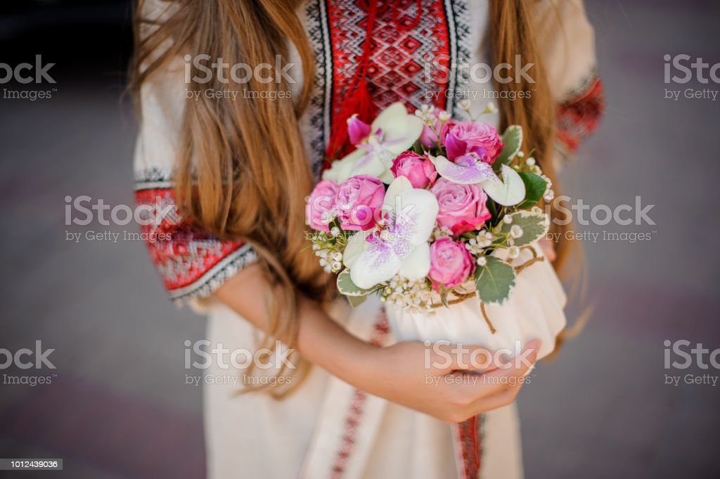 Long haired woman in national ukrainian blouse embroidery holding a cute white pot of pink and red roses stock photo